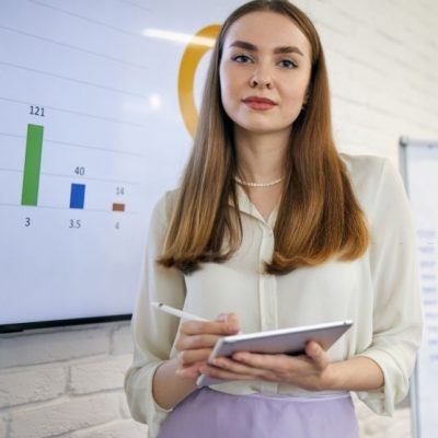 Modern young business woman having leading a presentation while using the wealth of technology to explain a statistic in a board room